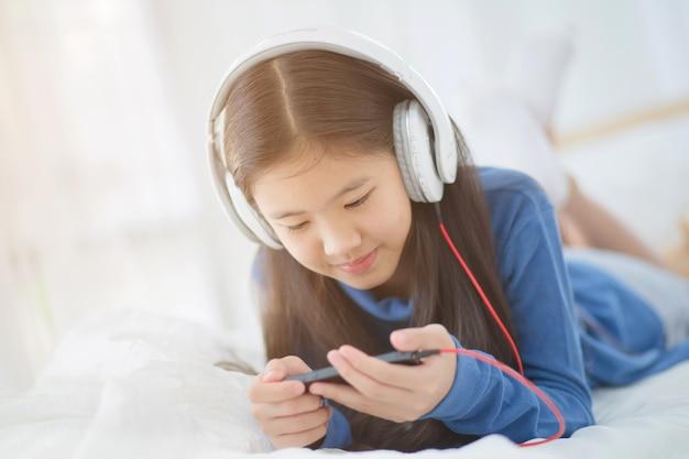 Ragazza piuttosto asiatica utilizzando la cuffia per ascoltare ...