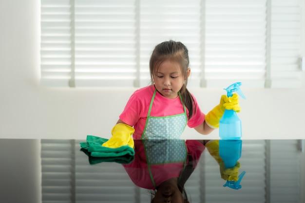 Ragazza prescolare sveglia asiatica dello studente che lava tavola di vetro con l'asciugamano verde in salone a casa, con spruzzo della soluzione detergente e dell'acqua. Foto Premium