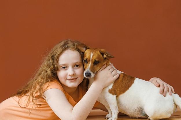 Ragazza riccia che abbraccia il suo cane amico. Foto Premium
