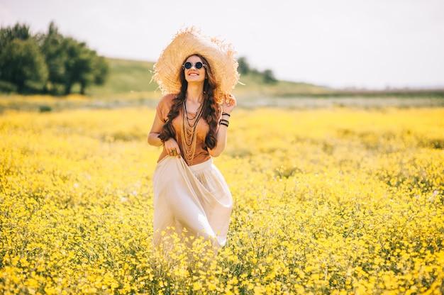 Ragazza romantica hippie in piedi in un campo. estate. stile hippie Foto Premium