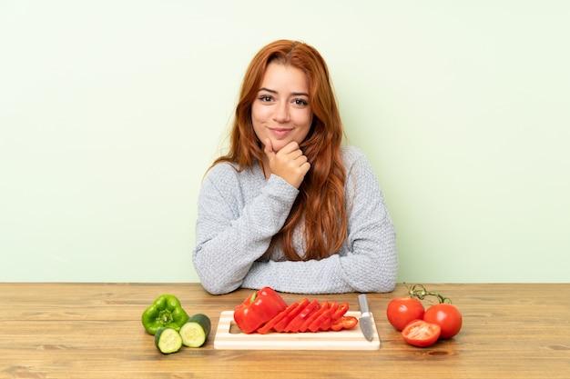 Ragazza rossa adolescente con verdure in una risata del tavolo Foto Premium