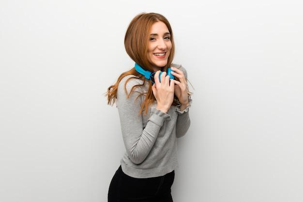 Ragazza rossa sul muro bianco con le cuffie Foto Premium