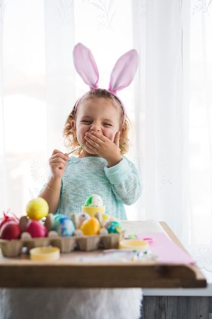 Ragazza sbadigliando colorare le uova Foto Gratuite