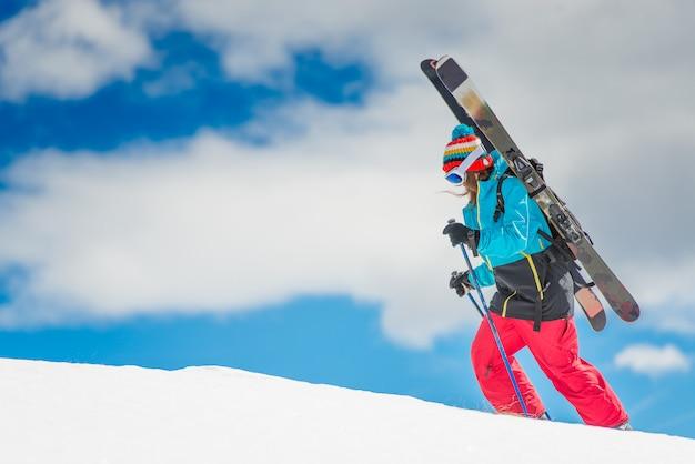 Ragazza sciatrice freeride, scala la montagna prima della discesa Foto Premium