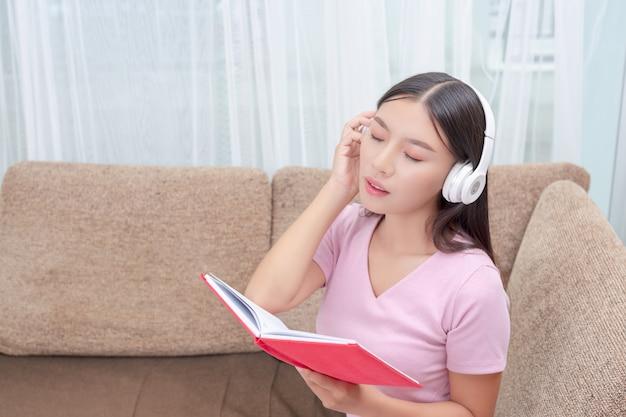 Ragazza sdraiata sul divano ascoltando musica e leggendo libri. Foto Gratuite