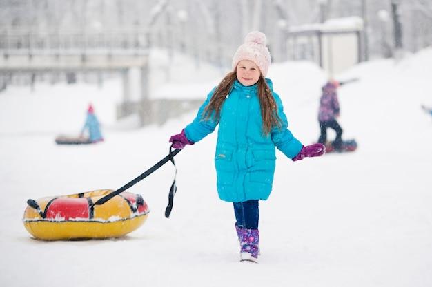 Ragazza si diverte sul tubo di neve. ragazza sta guidando un tubo. vacanze invernali, vacanze per bambini in inverno. parco cittadino invernale. Foto Premium