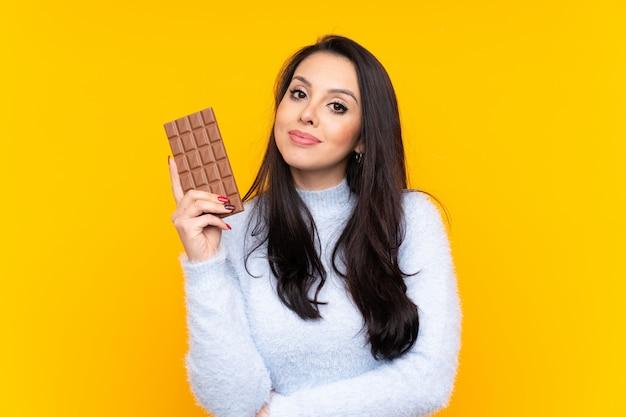 Ragazza sopra la parete gialla che prende una compressa del cioccolato e felice Foto Premium