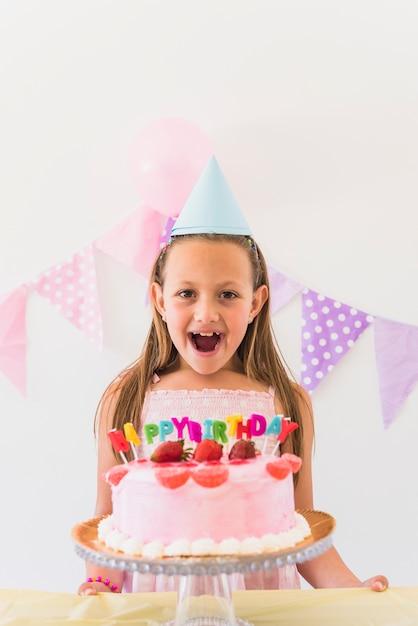 Ragazza sorpresa allegra di compleanno che si leva in piedi dietro la torta e le candele Foto Gratuite