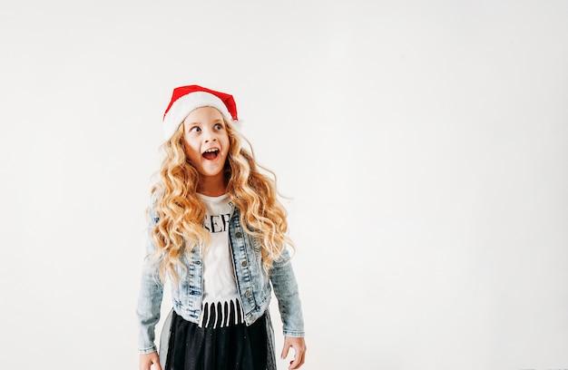 Ragazza sorpresa dell'interpolazione dei capelli ricci in cappello di santa e rivestimento del denim e gonna nera del tutu su bianco isolato Foto Premium