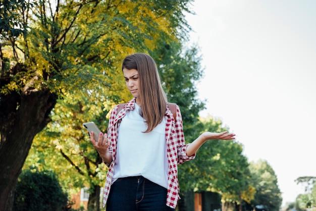 Ragazza sorpresa mentre controllando il suo telefono Foto Gratuite