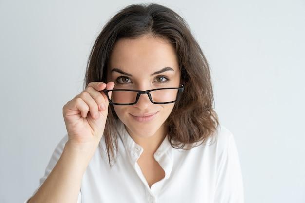 Ragazza sorridente allegra che rimuove i vetri. giovane donna caucasica sbirciare sopra gli occhiali. Foto Gratuite