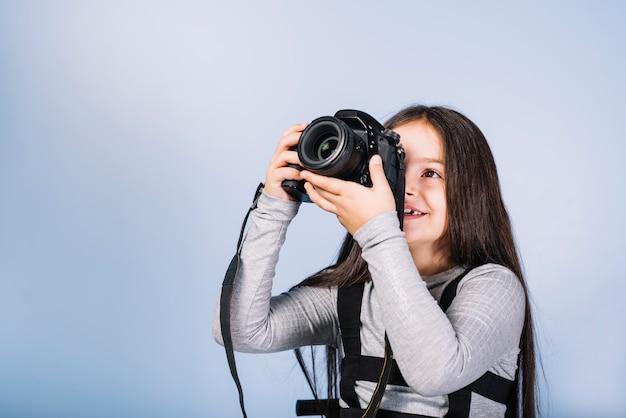Ragazza sorridente che fotografa attraverso la macchina fotografica contro la macchina fotografica blu Foto Gratuite