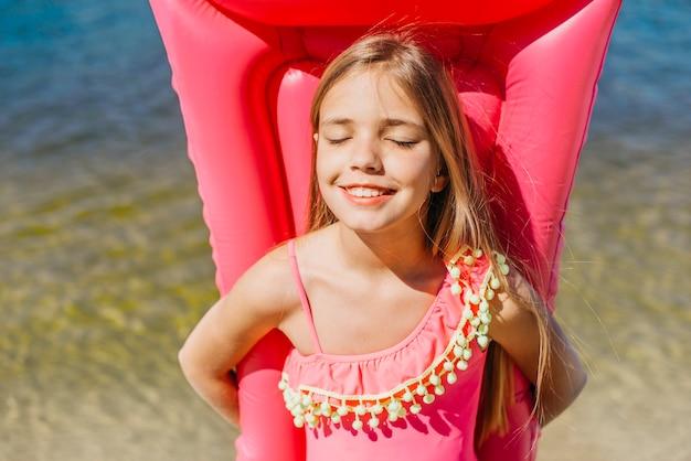 Ragazza sorridente che mantiene materasso gonfiabile che fa una pausa acqua Foto Gratuite