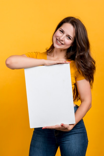 Ragazza sorridente che mostra un poster vuoto Foto Gratuite