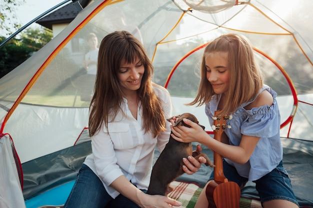 Ragazza sorridente che segna la tenuta del piccolo cane da sua madre che si siede in tenda Foto Gratuite