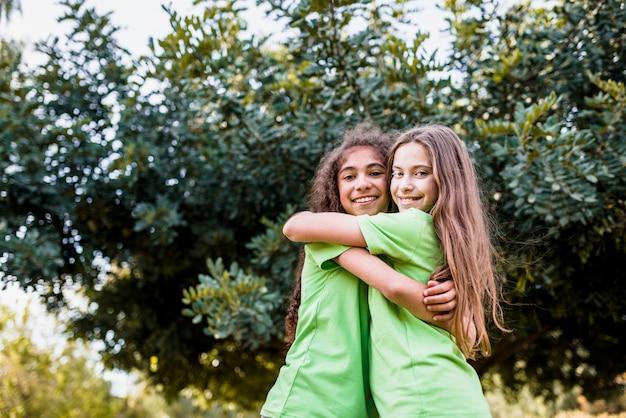 Ragazza sorridente che si abbracciano contro l'albero verde Foto Gratuite