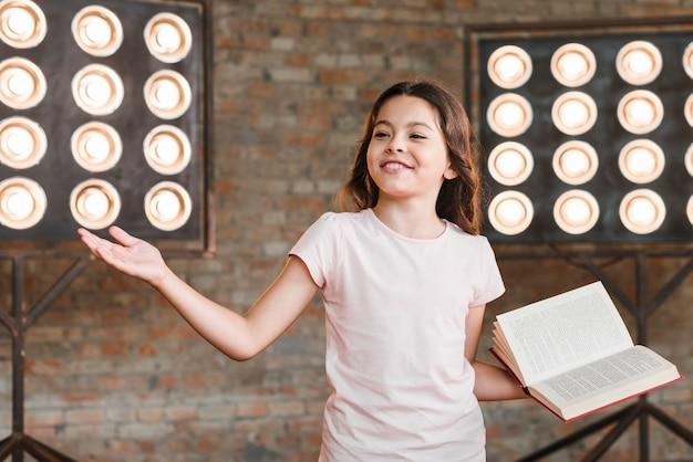 Ragazza sorridente che sta davanti alla luce della fase che dà la sua prestazione Foto Gratuite