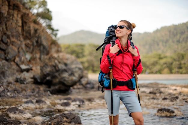 Ragazza sorridente che sta sulle rocce con l'escursione dello zaino Foto Premium