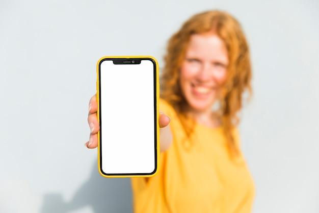 Ragazza sorridente che tiene smartphone Foto Gratuite