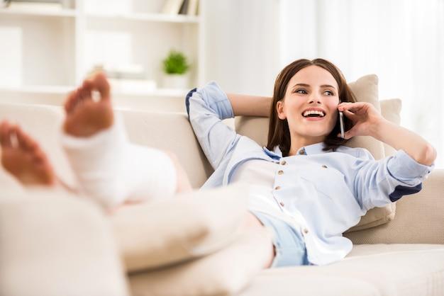 Ragazza sorridente con i gyps sulla gamba che pone sul sofà. Foto Premium