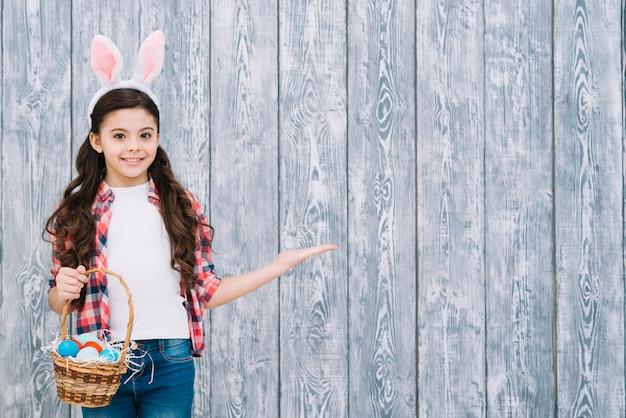 Ragazza sorridente con le orecchie del coniglietto che tiene canestro delle uova di pasqua che presentano contro lo scrittorio di legno grigio Foto Gratuite