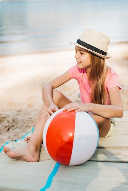 Ragazza sorridente con palla di vento in spiaggia Foto Gratuite