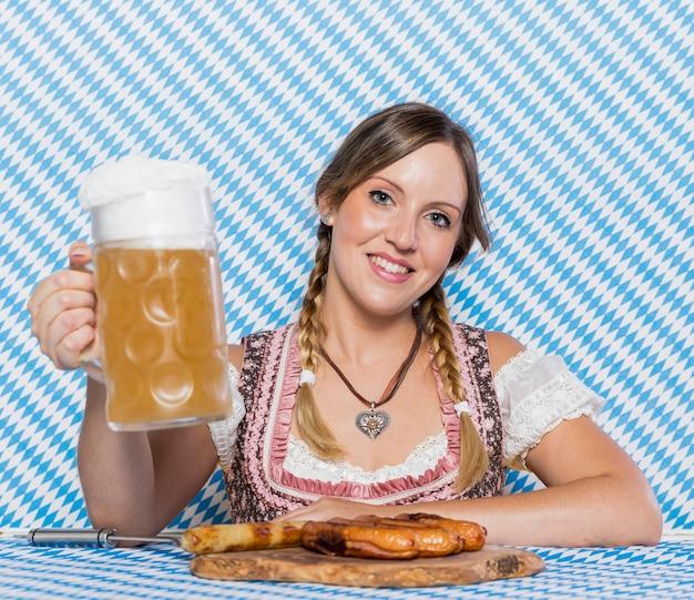 Ragazza sorridente con spuntini bavaresi Foto Gratuite