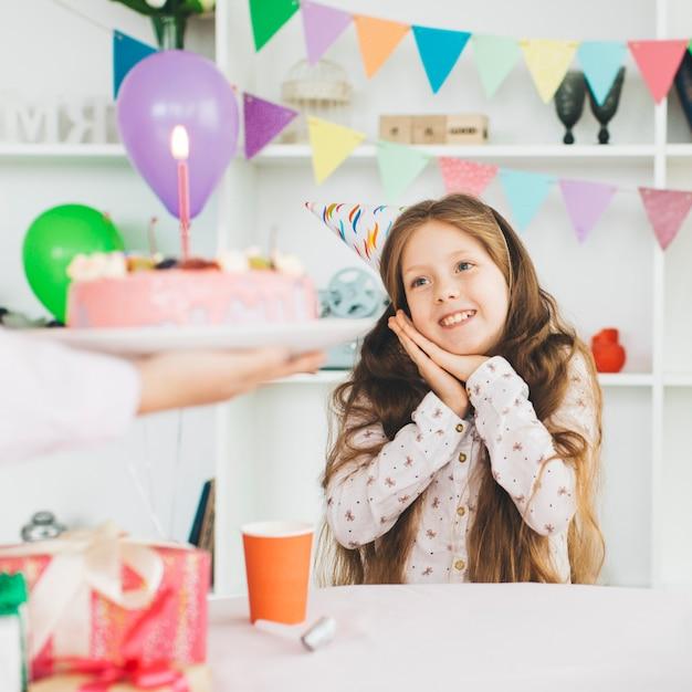 Ragazza sorridente con una torta di compleanno Foto Gratuite
