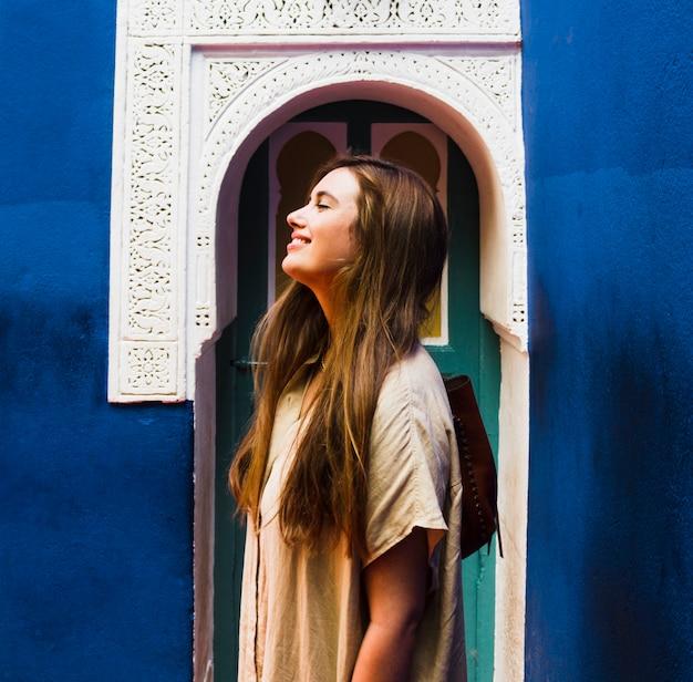 Ragazza sorridente davanti alla vista laterale della porta ad arco Foto Gratuite