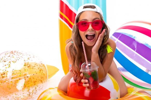 Ragazza sorridente del primo piano su una priorità bassa bianca, il bambino tiene i cocktail analcolici nelle sue mani e ride Foto Premium
