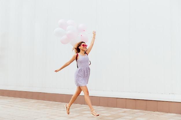 Ragazza sorridente emozionante in occhiali da sole rosa in esecuzione con palloncini, indossando abiti e sandali Foto Gratuite