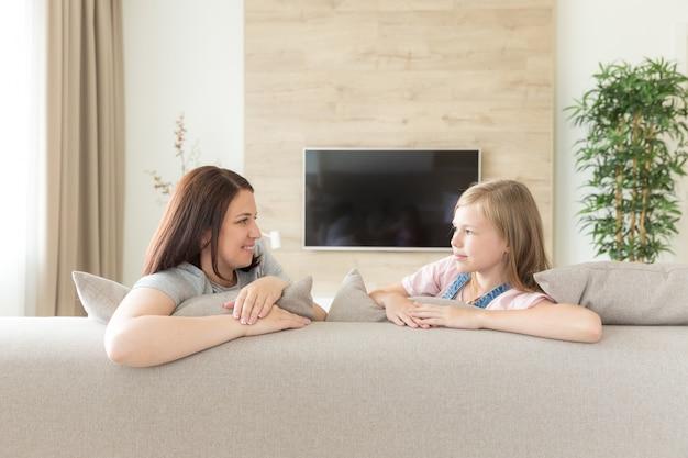 Ragazza sorridente felice di concetto nucleo familiare e della gente con la madre che abbraccia sul sofà a casa Foto Premium