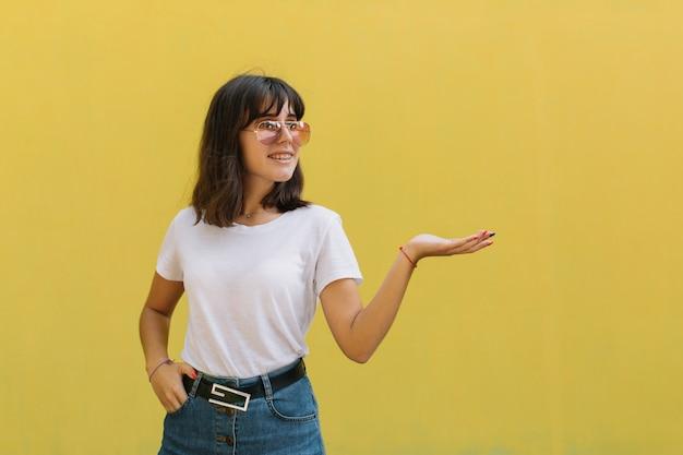 Ragazza sorridente in vetri e parentesi graffe mentre levandosi in piedi da solo contro una priorità bassa gialla. Foto Premium