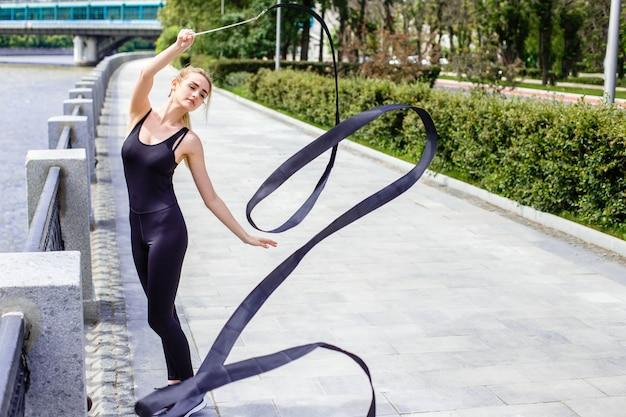 Ragazza sottile alla moda in strada con un nastro di ginnastica Foto Premium