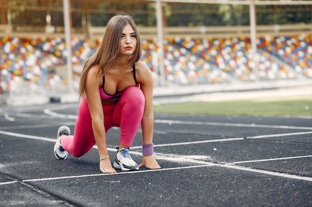 Ragazza sportiva in uniforme rosa corre allo stadio Foto Gratuite