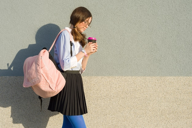 Ragazza studentessa con zaino scuola e bicchiere di bevanda Foto Premium