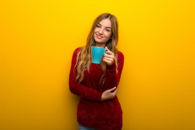 Ragazza su giallo vibrante che tiene una tazza di caffè calda Foto Premium