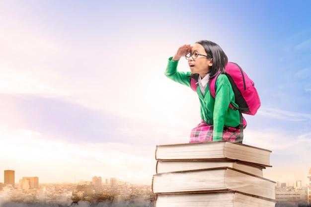 Ragazza sveglia asiatica con i vetri e lo zaino che si siedono sulla pila di libri con la città e il cielo blu Foto Premium