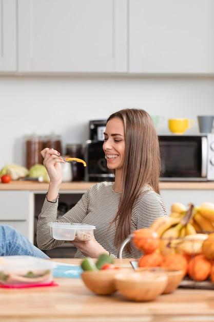 Ragazza sveglia che osserva e che sorride al suo alimento Foto Gratuite