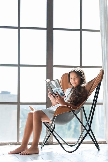 Ragazza sveglia che si siede sul libro di lettura della sedia Foto Gratuite