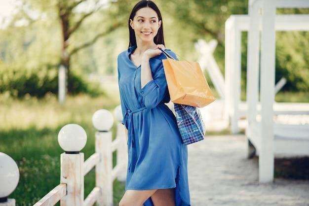 Ragazza sveglia con il sacchetto della spesa in un parco Foto Gratuite