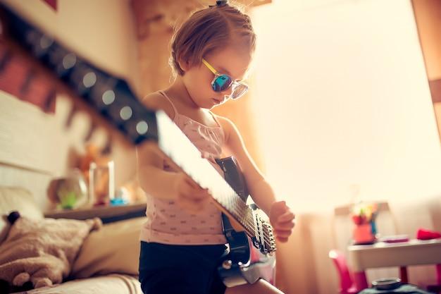 Ragazza sveglia del piccolo bambino in occhiali da sole che gioca chitarra. Foto Premium