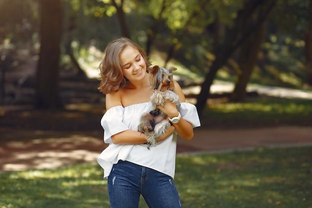 Ragazza sveglia in camicetta bianca che gioca con il piccolo cane Foto Gratuite
