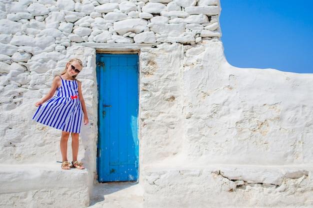 Ragazza sveglia in vestito blu divertendosi all'aperto vicino alla chiesa di paraportiani. scherzi alla via del villaggio tradizionale greco tipico con le pareti bianche e le porte variopinte sull'isola di mykonos, in grecia Foto Premium