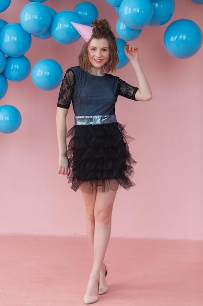 Ragazza teenager nel cono di compleanno in posa sul muro rosa e sullo sfondo di palloncini blu. Foto Gratuite