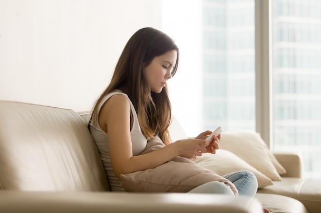 Ragazza teenager triste che per mezzo del telefono mentre sedendosi sul sofà Foto Gratuite