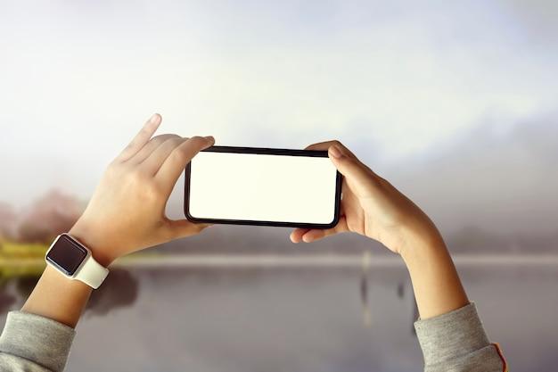 Ragazza turistica che cattura foto con il telefono cellulare sul bellissimo paesaggio Foto Premium