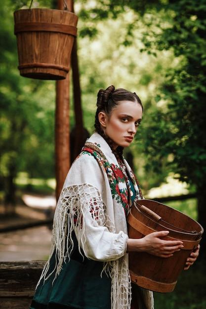 Ragazza ucraina affascinante in un abito tradizionale con un secchio in braccio Foto Gratuite