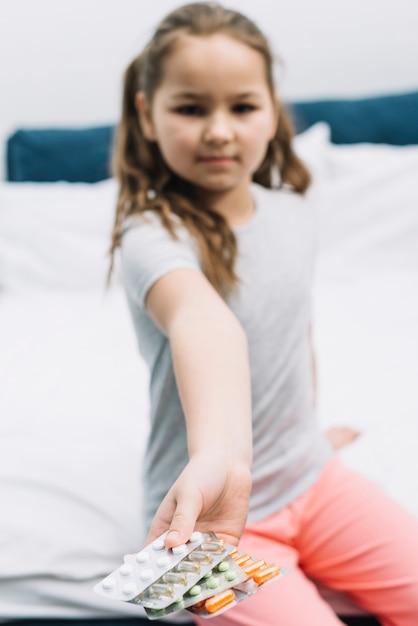 Ragazza vaga che si siede sul letto che mostra tipo differente di blister delle pillole Foto Gratuite