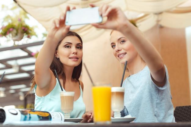 Ragazze alla moda fresche che prendono un selfie nella caffetteria Foto Premium